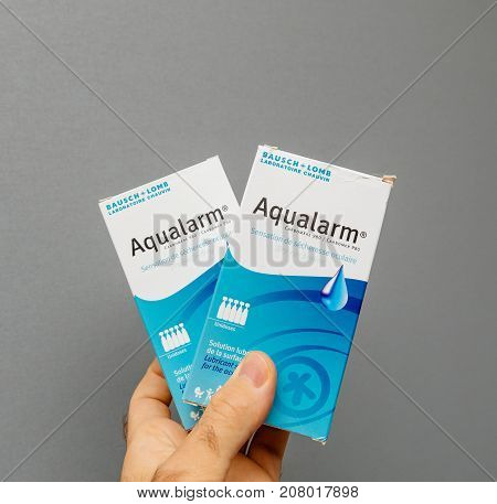 PARIS FRANCE - OCT 4 2017: Man holding eyedrops Aqualarm made by Bausch and Lomb Laboratorire Chauvin - gray background