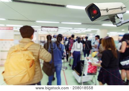 hand holding mobile phone and CCTV security indoor camera system operating with blurred image of people at immigration control at airport internet surveillance security safety technology concept