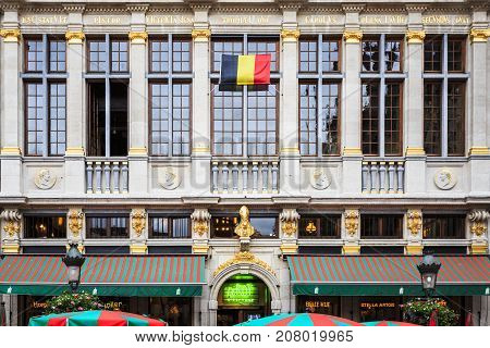 BRUSSELS BELGIUM - JUNE 18 2016: One of the restaurants located in the Grand Place LeRoy D'Espagne with a Belgium flag hoisted in the building's facade. Brussels Belgium.