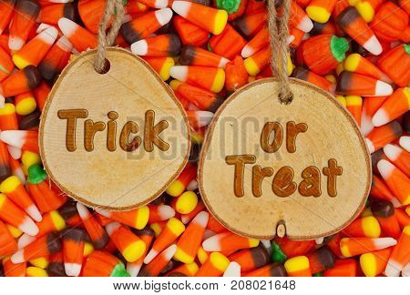Halloween Trick or Treat Greeting on wood plaque with candy corn background