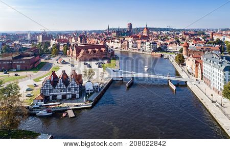 Gdansk Poland. Aerial skyline panorama with Motlawa river modern drawbridge concert hall and all famous monuments in the background: medieval crane St Mary and St John churches city hall tower