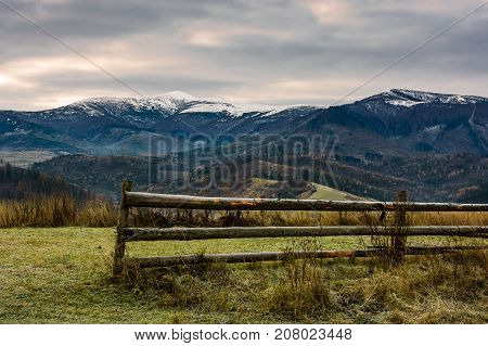 Fence On Grassy Meadow In Autumn