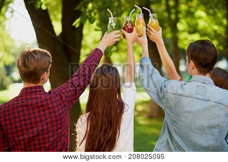 Group of people do cheers with detox juice cocktails on green nature background witn free space. Diet on the go, well being and weight loss, superfoods, health, victory concept