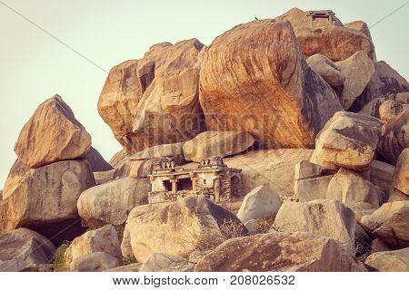 Old temple between stones in Hampi, Karnataka, India. Vintage color filter applied