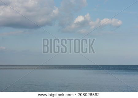 light wind blows cumulus clouds over water surface of Lake Ladoga and the sky joins with surface of water on the horizon Russia Leningrad region