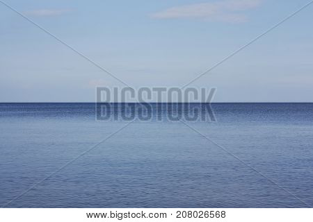 blue water of Ladoga Lake connects with light blue sky on horizon. Russia Leningrad region