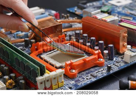 Electronic service center, technology maintenance concept. Computer processor chip disassembling in repair shop close up.