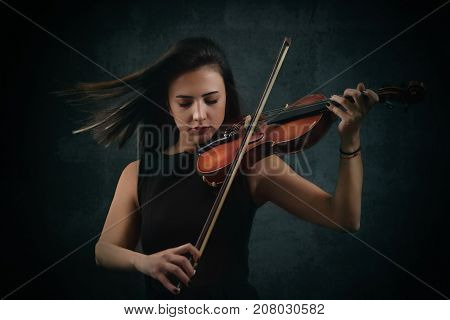 Beautiful Violinist Woman playing violiln on black background