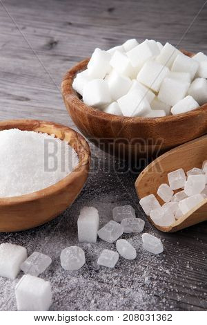 Bowl with white sand crystal and lump sugar on wooden background.