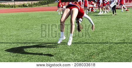 A cheerleader is practicing back flips while getting ready for homecoming at a local high school.