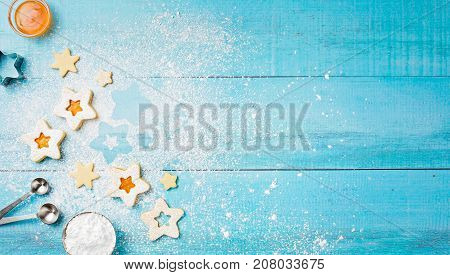 Decorating Christmas Linzer cookies with icing sugar and apricot jam on a blue wooden background.