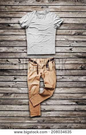 Brown jeans trouser and shirt over wood background