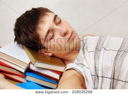 Tired Student sleep on the Sofa with the Books