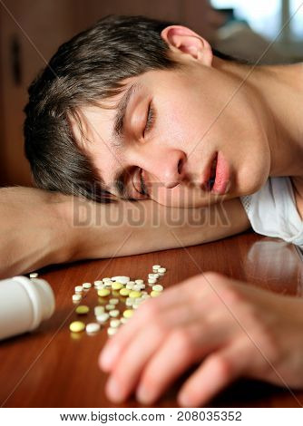 Young Man sleep with a Pills at the Home