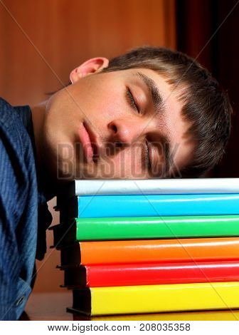 Tired Student sleep on the Books at the Home