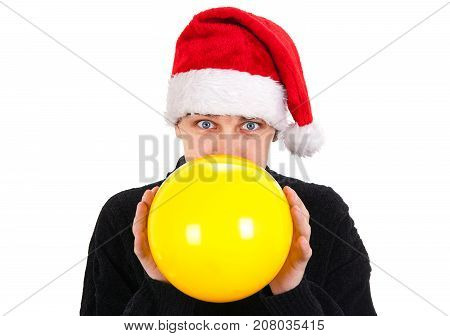 Young Man in Santa Hat inflate a Yellow Balloon on the White Background