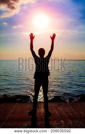 Toned Photo of Happy Person Silhouette at the Sunset on the Sea Background