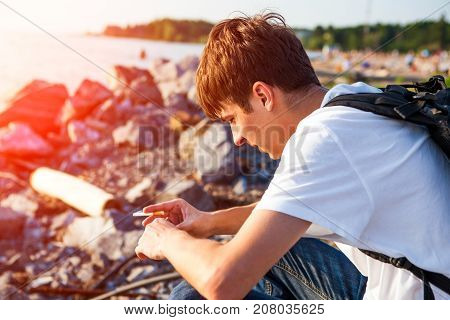 Sad Young Man sit at the Seaside with Cigarette