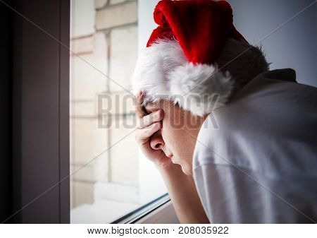 Sad Teen in Santa's Hat by the Window