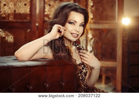 Girl fashion model with stunning make-up, fresh skin and beautiful hair. Beauty portrait. A woman in a leopard dress. Trendy, modern female.