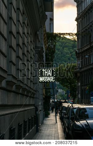 Narrow street at sunset with a Thai massage sign in Budapest. Budapest Hungary - September 25 2017: Late afternoon perspective view of narrow street with parked cars in Budapest Hungary. Incidental people walking down the street to get to the Danube river