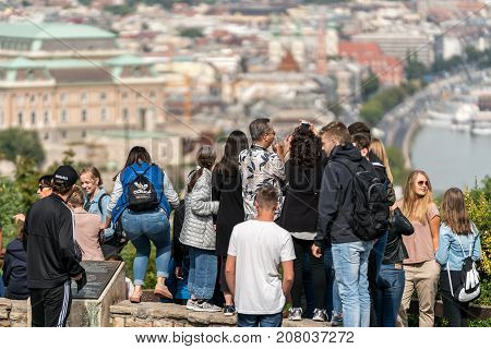 Group of tourist at a viewpoint above Budapest. Budapest Hungary - September 26 2017: Selective focus back view of a mixed group of young and old tourists standing at a viewpoint up high to take panoramic pictures of the city Budapest Hungary below.