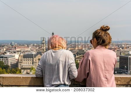 Two young woman looking down on city of Budapest. Budapest Hungary - September 26 2017: Close up back view of two young caucasian woman leaning over stone railing to relax and to look at the city view of Budapest Hungary in the background.