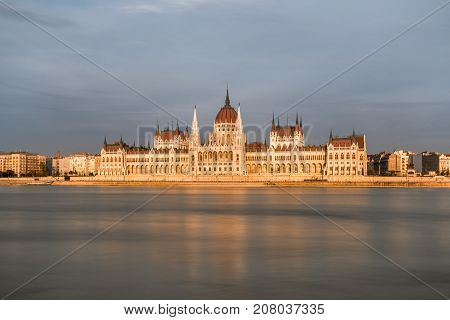 The famous parliament building in Budapest. Budapest Hungary - September 26 2017: Long exposure sunset front view of the Hungarian Parliament in Budapest by the Danube river. Surrounding buildings and incidental people with a tram stop below the building.