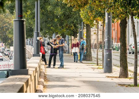 Young couple on city walkway looking at a map. Budapest Hungary - September 27 2017: Side view of a caucasian couple standing on a walk and cycle path in Budapest Hungary looking at a city map to find direction. Autumn trees traffic and incidental people