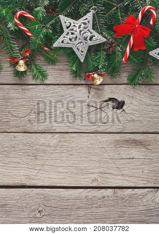 Xmas decoration border background. Fir tree branches border with star, candy canes and bells top view with copy space on gray rustic wooden table. Christmas ornaments frame for any winter holiday