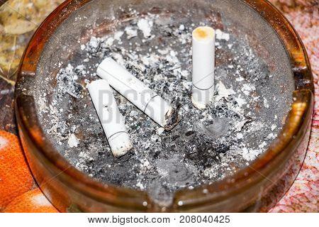 Three cigarette butts in the dark ashtray