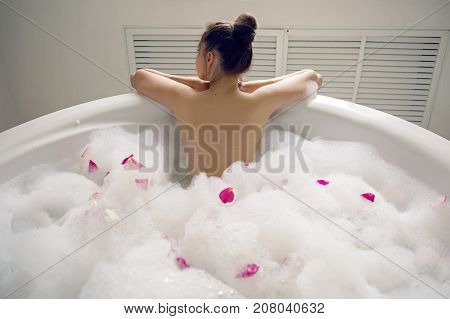 girl lying on belly in a large round white bath with foam and rose petals