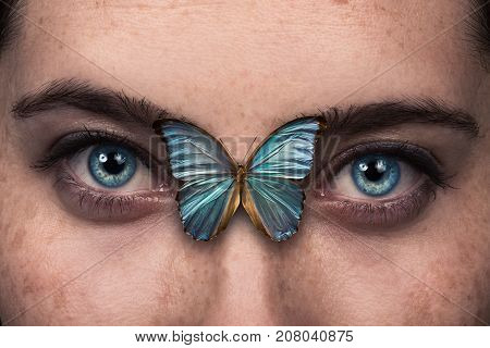Beautiful woman eye with blue butterfly wing