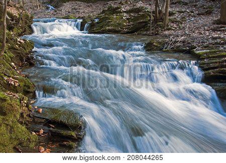 Fast flowing water in the creek between the stones.