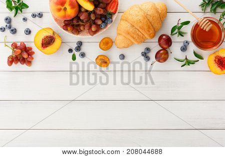 Rich continental breakfast background. French crusty croissants, lots of sweet berries and honey for tasty morning meals. Delicious start of the day. Top view with copy space on white wooden table