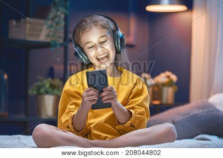 Little girl with headphones on the bed at home. Child girl listening to music.