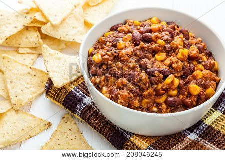 Bowl of chili con carne and corn nachos close-up