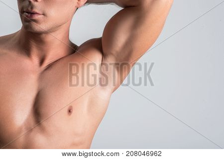 Enjoying his perfect form. Close-up of smooth armpit of young muscular guy. He is standing naked while raising his arm up. Isolated background and copy space in right side