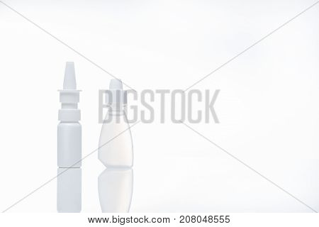 Wellness concept. Close-up of health care subjects. Nasal spray and eye drops are on desk. Isolated background and copy space in the right side