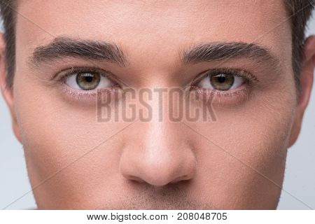 Male beauty concept. Close-up of face of young attractive man is looking at camera confidently. Focus on eyes. Isolated background
