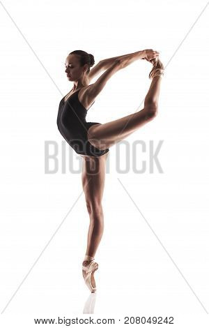 Ballerina in black outfit posing on toes. Isolated on white background