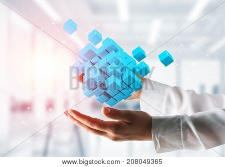 Cropped image of businessman hands holding multiple light blue cubes in hands with sunlight on office background. Mixed media.
