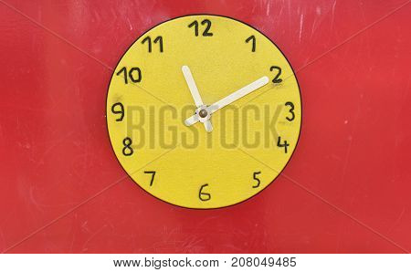 Wooden big yellow clock in children playground. Time abstraction.