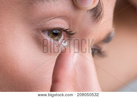 Medicine and vision concept. Close-up of eye of young man who is putting contact lens to correct visual effect