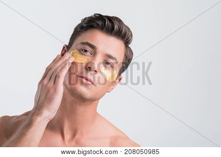 Close-up portrait of naked young man who is applying golden collagen patches under his eyes. He is looking aside thoughtfully while touching his face. Copy space in the right side. Isolated