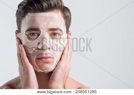 Skin care concept. Close-up portrait of young pleasant man is applying sheet mask while touching his face. He is looking at camera with confidence. Isolated and copy space in the right side