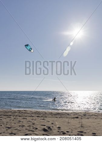 The unrecognizable bold kitesurfer rides on sea water on a board with a blue kite in bright sunlight and glare on the water