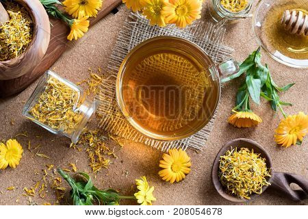 A Cup Of Calendula Tea With Calendula Flowers In The Background