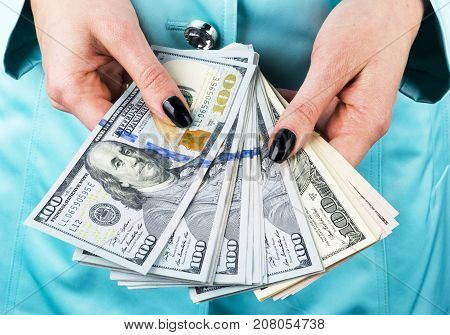 Business woman counting money in hands. Handful of money. Offering money. Women's hands hold money denominations of 100 dollars. Cash out money. Credit concept.