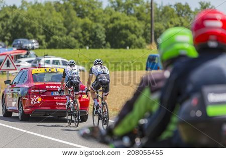 Mailleroncourt-Saint-Pancras France - July 5 2017: Rear image of two cyclists (Nikias Arndt and Warren Barguil of Team Sunweb) riding behind a technical car on a road to La Planche des Belle Filles during the stage 5 of Tour de France 2017.